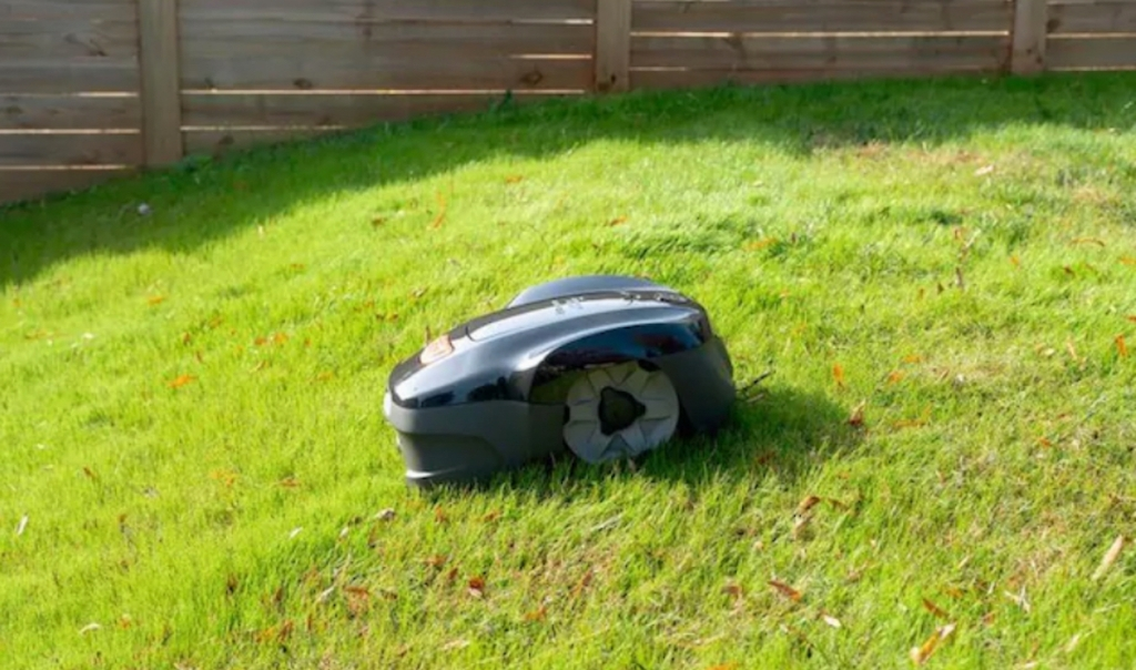 lawn mover going down grassy slope with fence