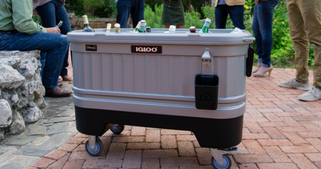 Igloo Cooler Bar Cooler on wheels outside on a patio with people standing behind it