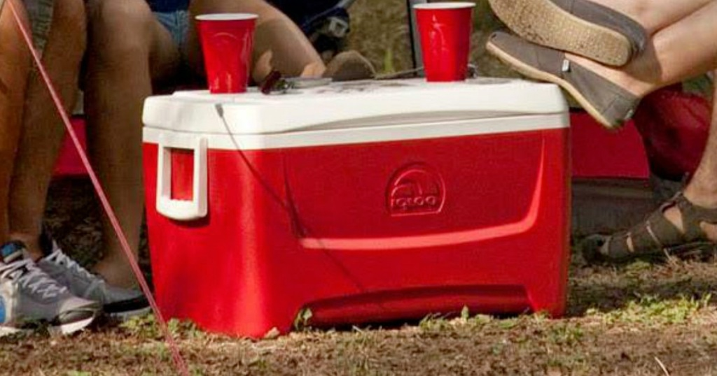 red igloo cooler with white lid and handles sitting outside with two red cups sitting on top of lid