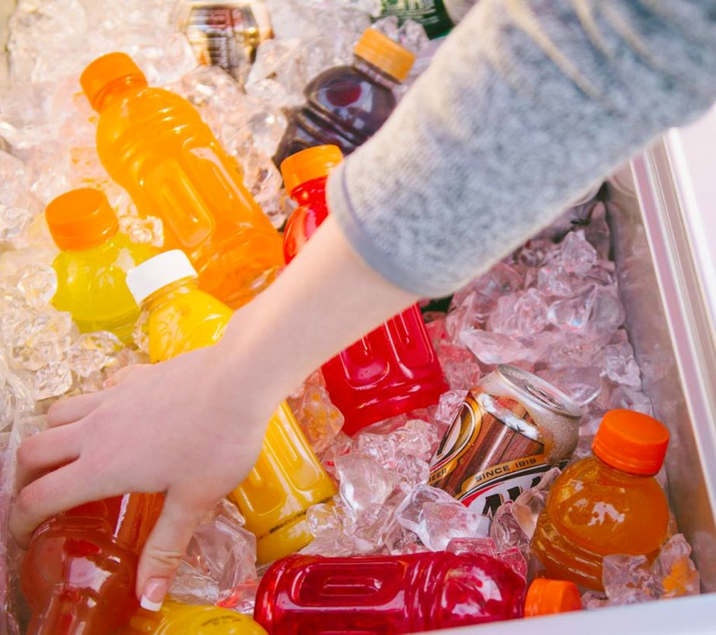 person reaching into cooler filled with ice and various soda and bottled drinks