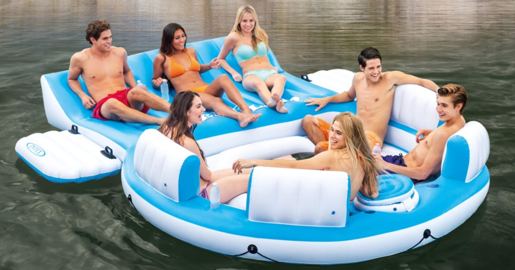 four adults sitting on intex floating lounge floating in river