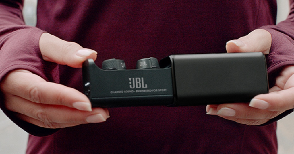 woman's hands holding JBL charging case open showing earbuds