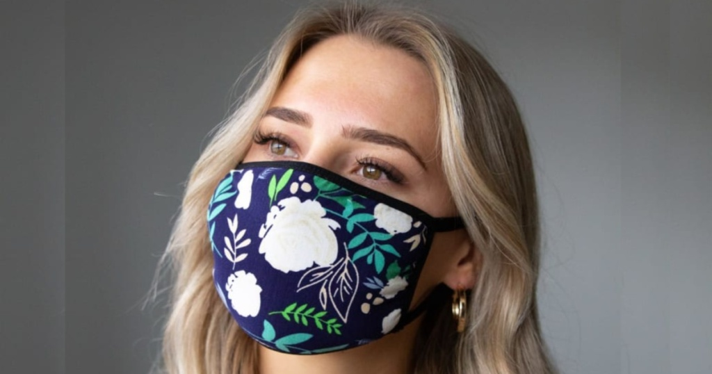 woman with blond hair wearing navy and flower printed face maks