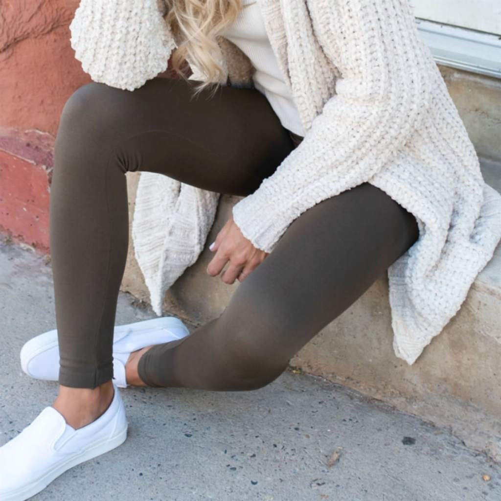 woman wearing coffee brown jane leggings sitting on cement bench wearing white shoes and cream cardigan