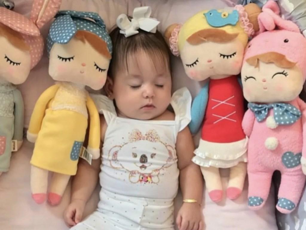 baby girl sleeping with stuffed dolls