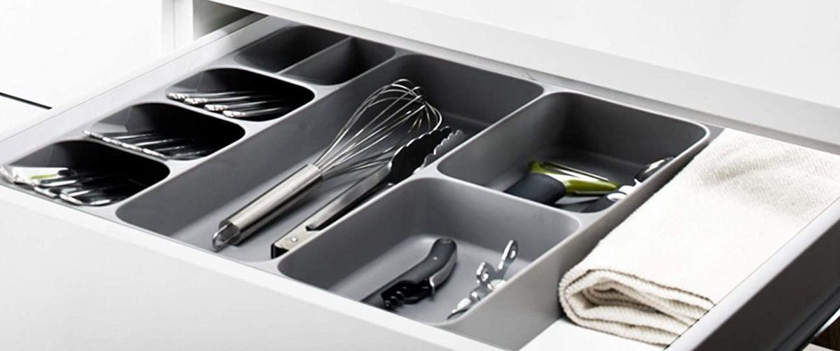 utensils in gray organizer tray in kitchen drawer