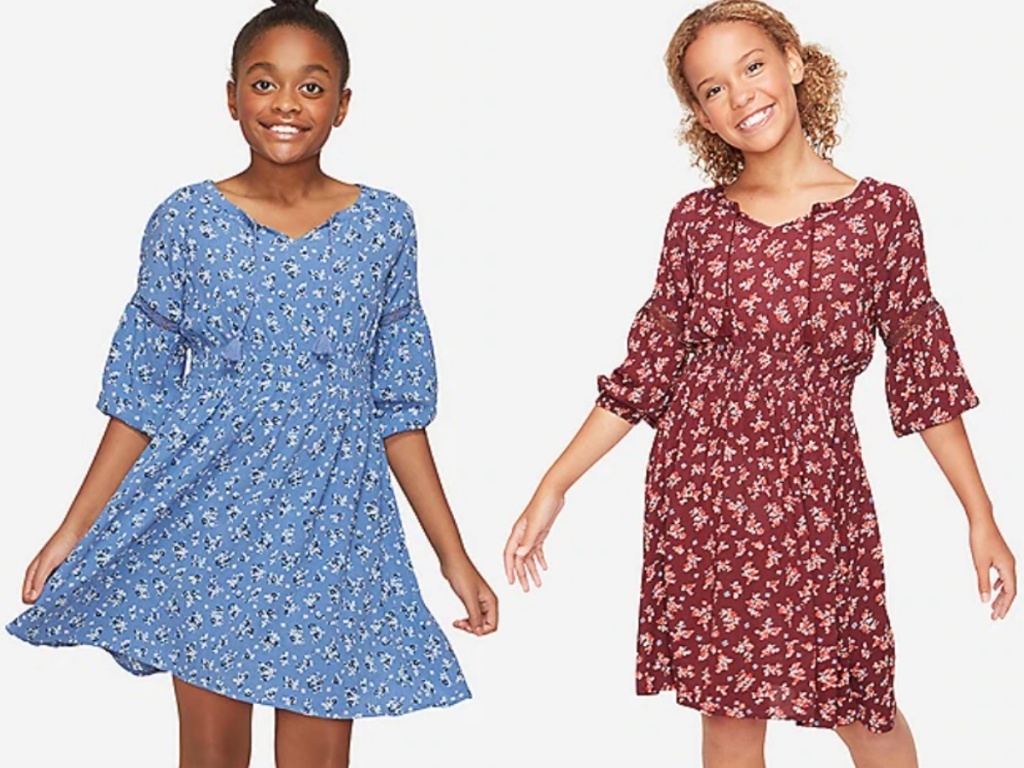 2 girls standing next to each other wearing floral peasant dresses