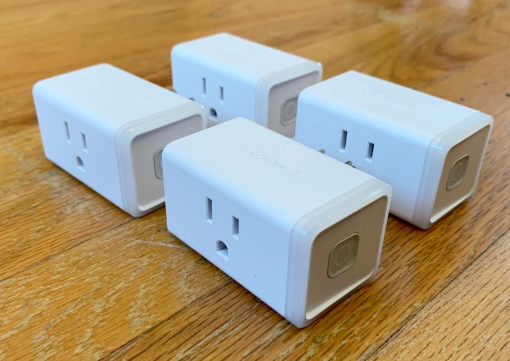 four white smart plugs sitting on wood table