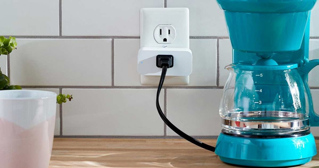 teal colored coffee pot plugged into a white smart plug on white tile backsplash