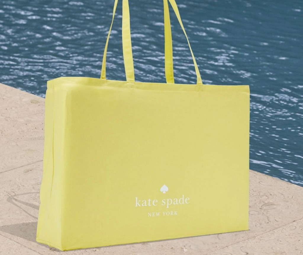 Large Kate Spade shopper tote bag in yellow next to a pool