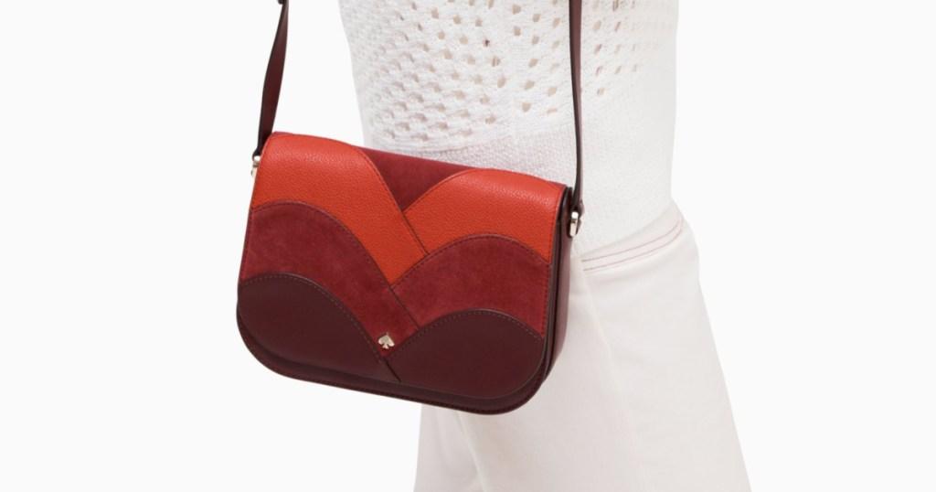woman wearing white carrying red kate spade bag