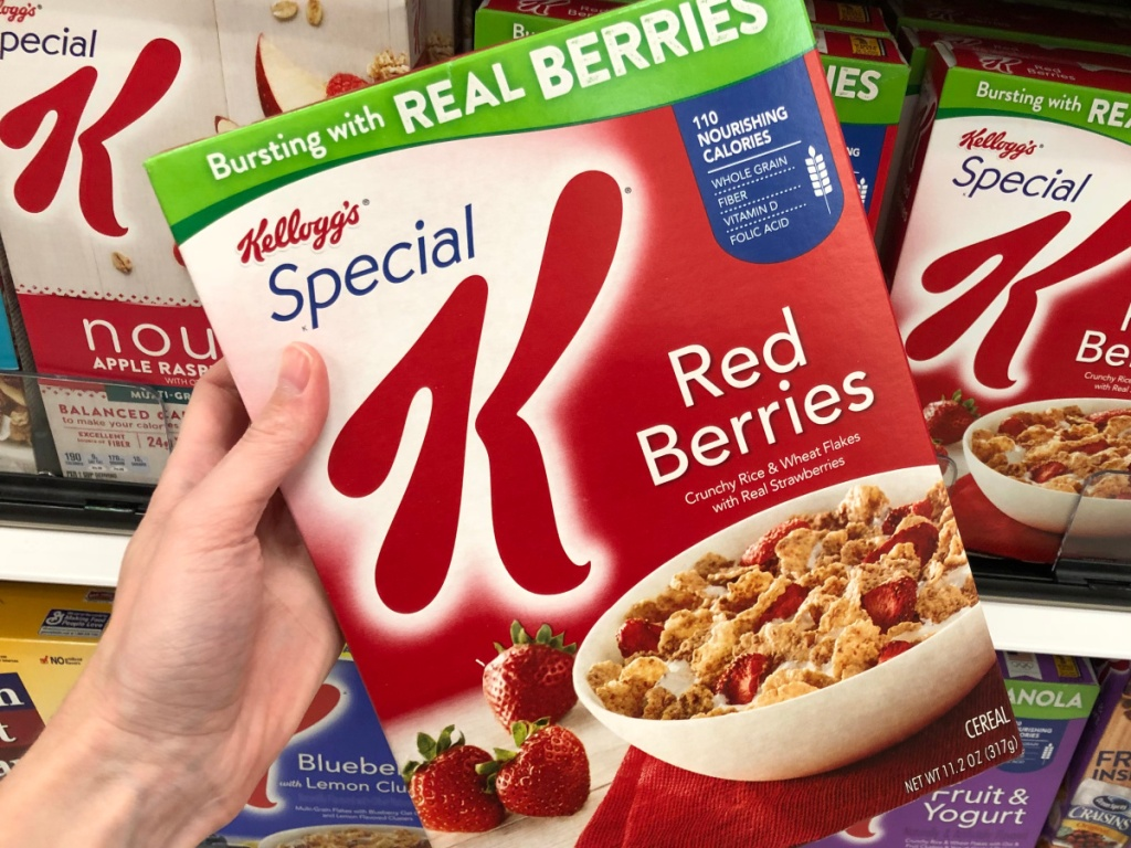 hand holding box of red berries cereal in store