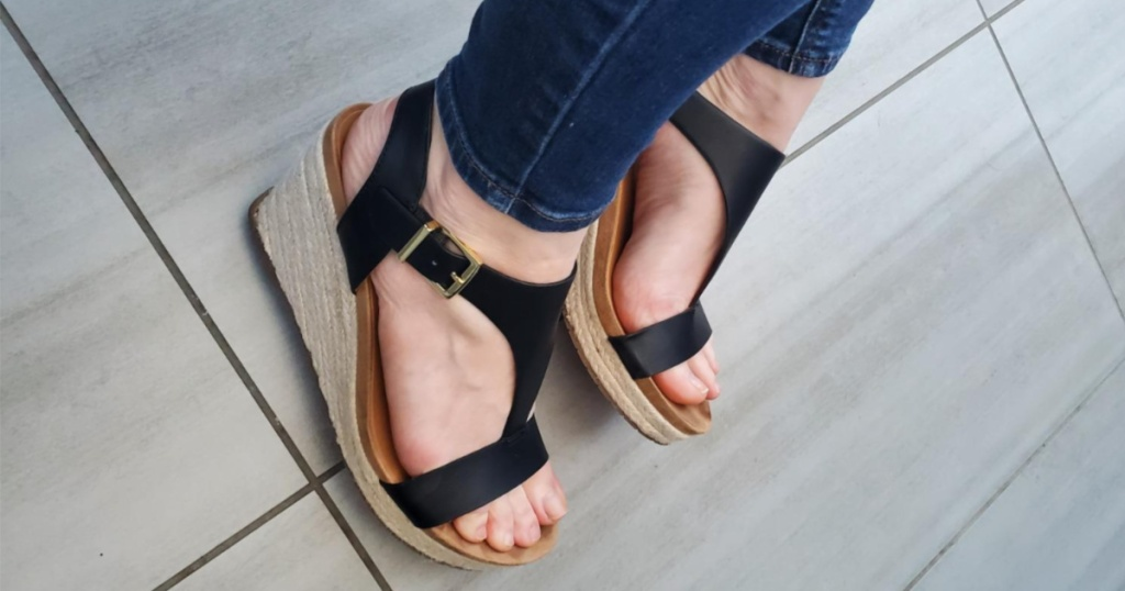 dark jeans and feet wearing black open-toed sandals with side buckle strap and wedge heel