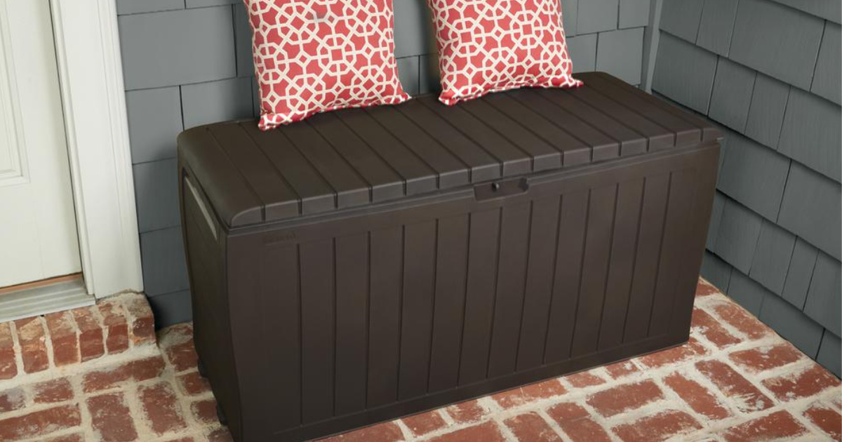 brown deck box on brick patio with pillows on deck box