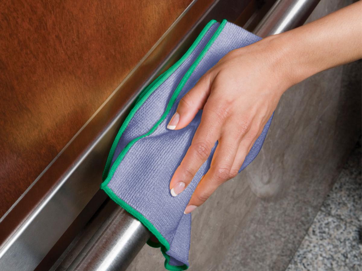 woman's hand using microfiber cloth on dishwasher handle