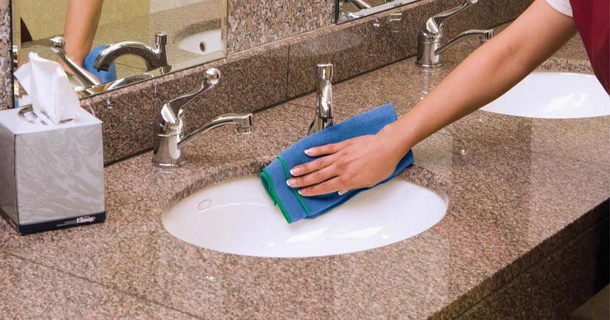 woman using microfiber cloth on bathroom sink