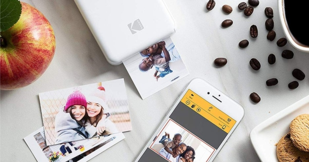 cell phone, photos, white photo printer, coffee, apple, and cookies on white table