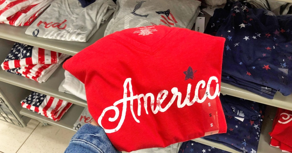 person holding up a red shirt that says America on it in white in front of display of other patriotic tees