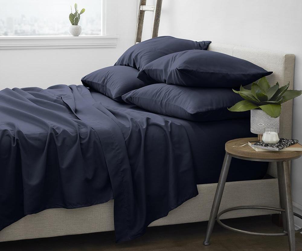 bed with navy sheets and pillows on it