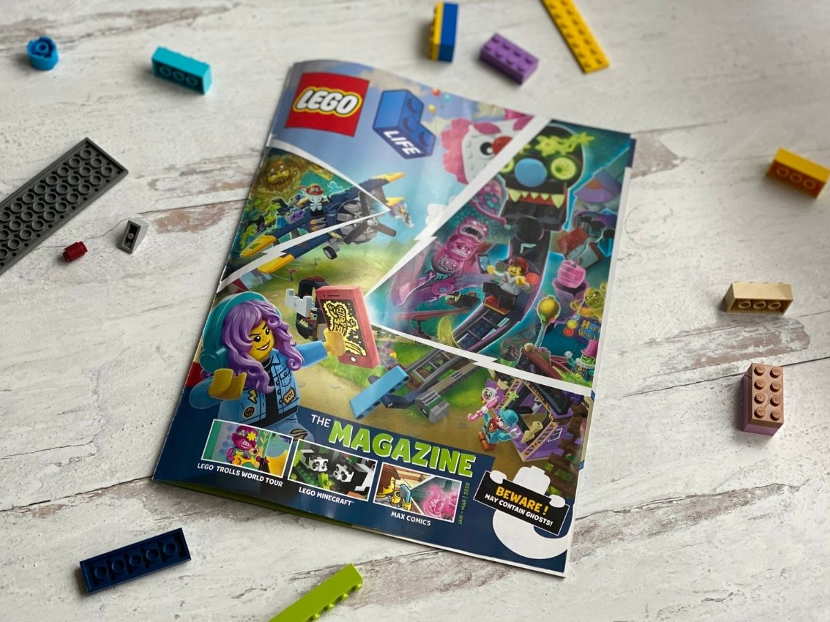 LEGO magazine on wood surface with LEGO pieces scattered around