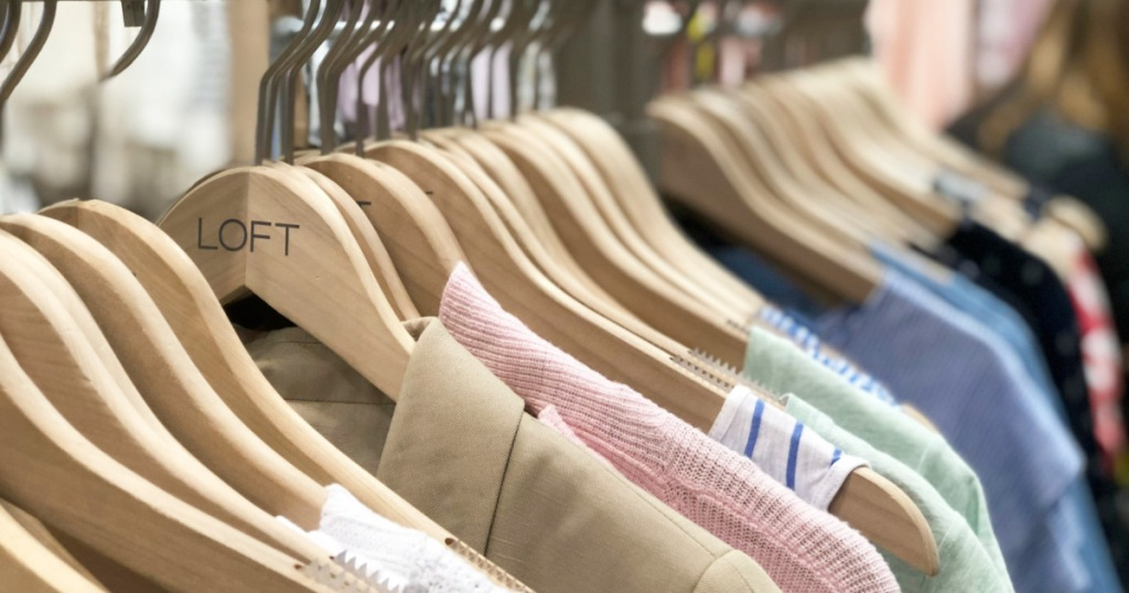 clothing hanging on wooden hangers that say LOFT