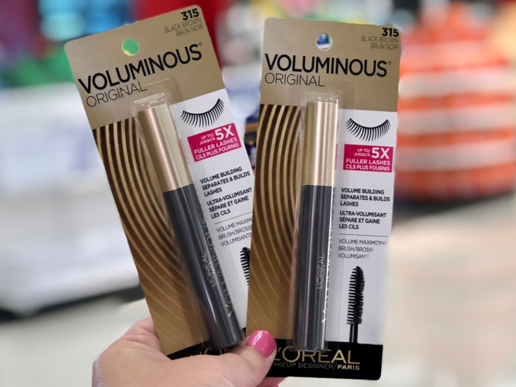 hand holding two mascaras in store