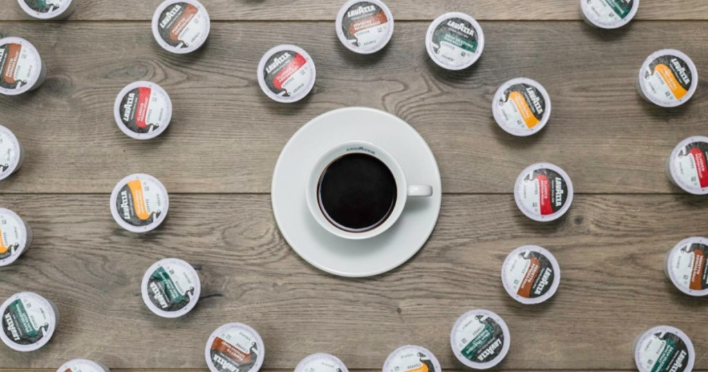 various flavored coffee pods surrounding cup of coffee on wood table