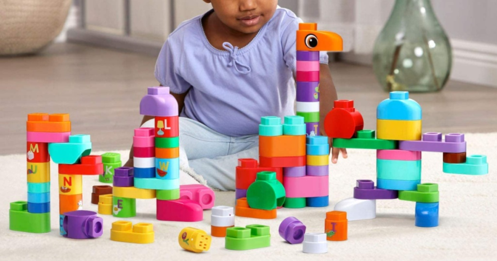 girl playing with building block set on carpet in home