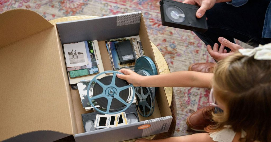 girl with brown hair placing a film reel into a cardboard box full of old photos and vhs tapes