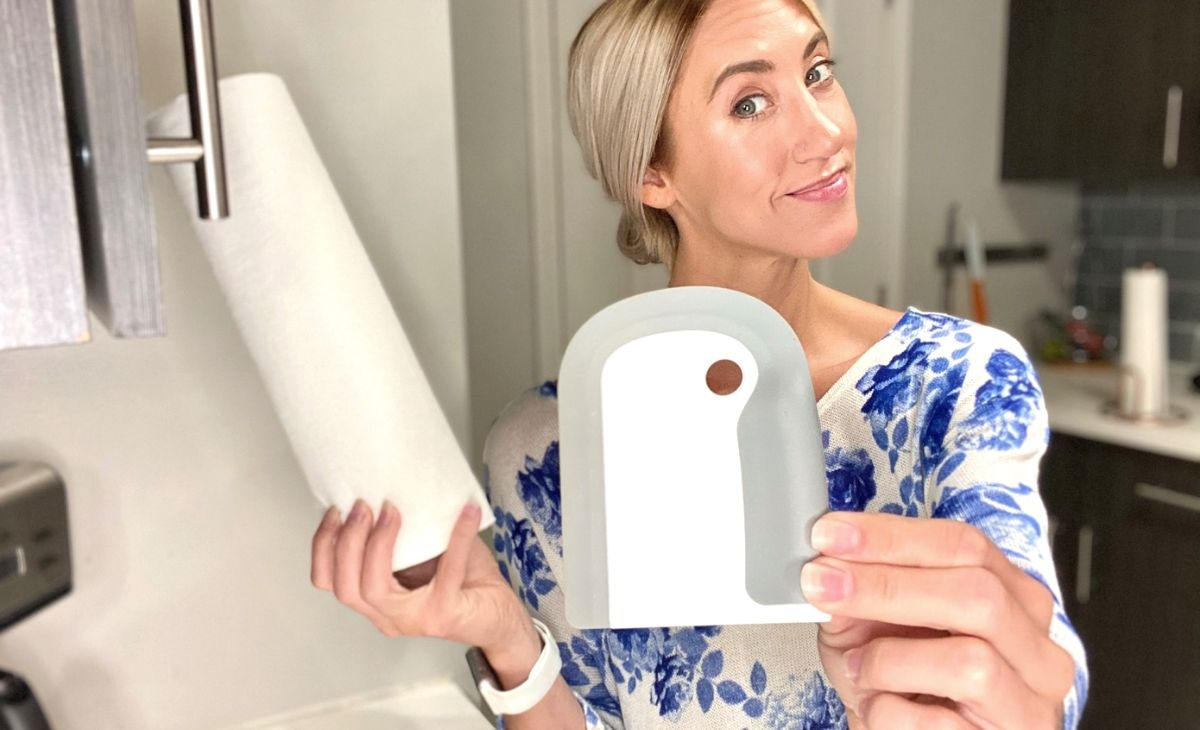Woman holding oxo dish squeegee in one hand and a roll of paper towels in the other hand