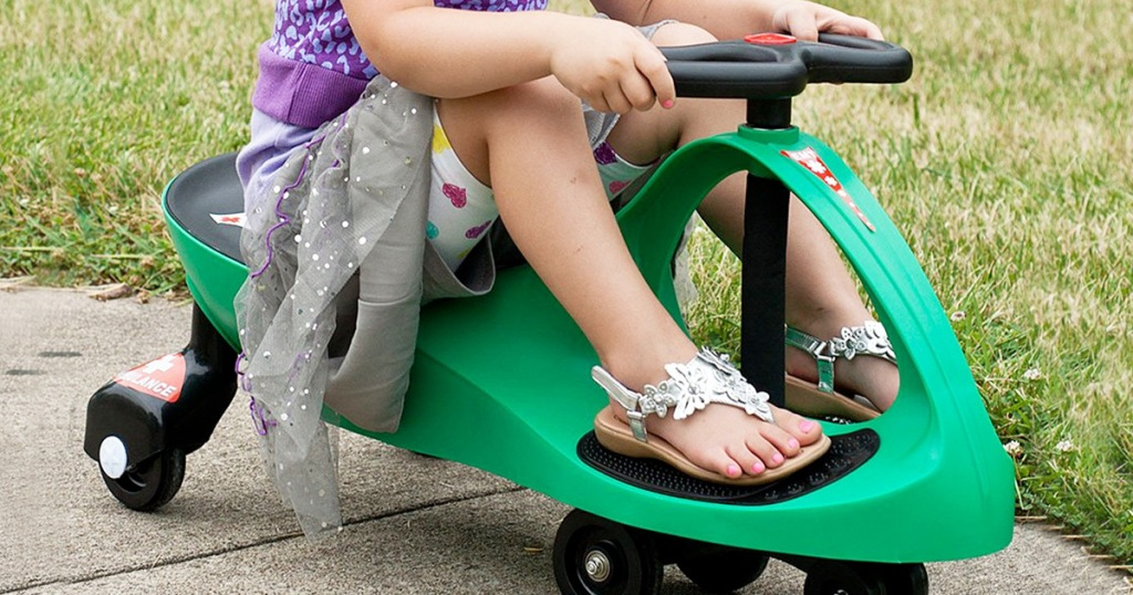 girl wearing grey skirt and sandals sitting on a green wiggle car on sidewalk