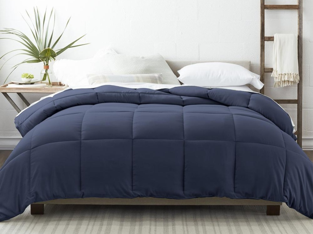 dark blue comforter on bed in bedroom