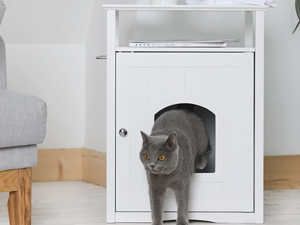 gray cat jumping out of white litter box table cover