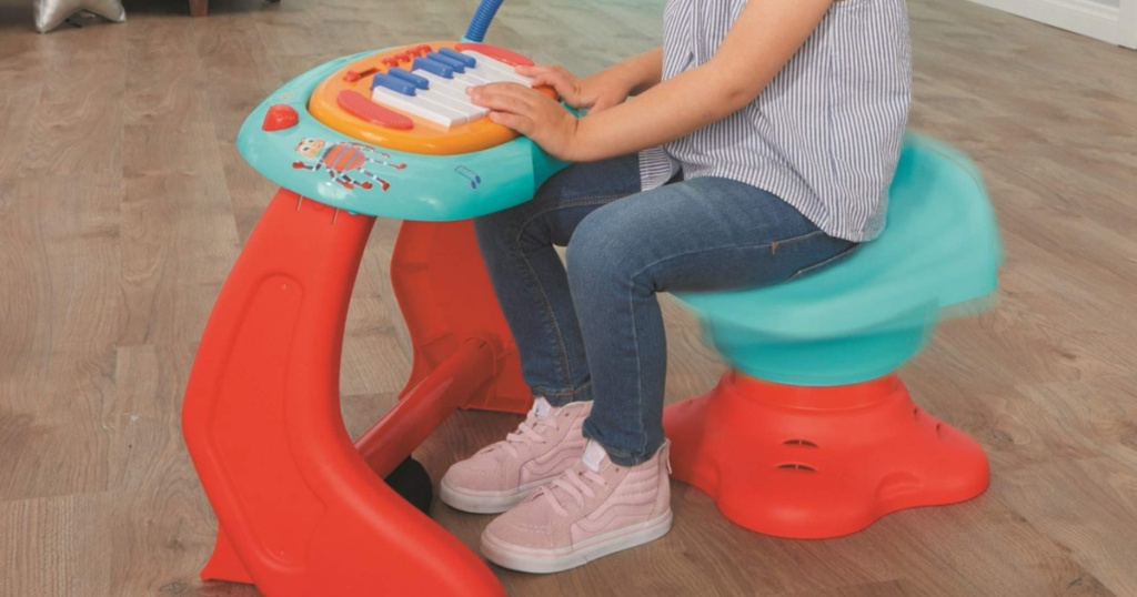 little girl sitting at a Little Tikes Baby Bum Sing Piano