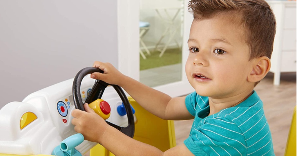 baby boy sitting in a activity climber pretending to drive