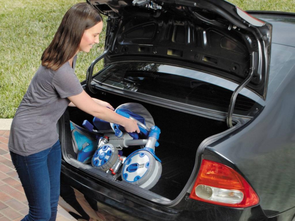 woman putting folded trike in trunk