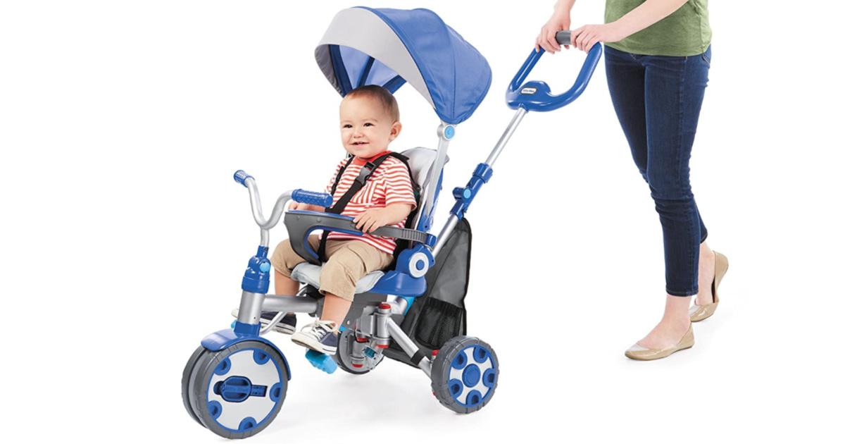 woman pushing kid in blue trike