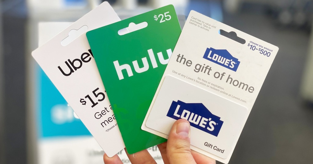 person holding three uber, hulu, and lowe's gift cards in hand