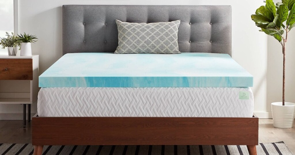 front view of white mattress with light blue swirl memory foam mattress topper on bed with wooden bedframe and grey headboard in bedroom with plants