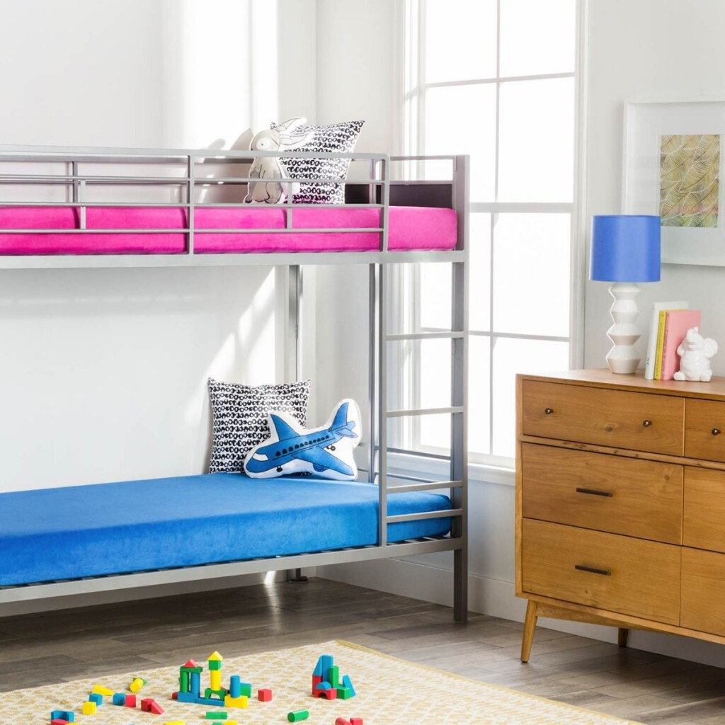 kids bedroom with bunkbeds. blue waterproof mattress on bottom and hot pink waterproof mattress on top with toys on the floor