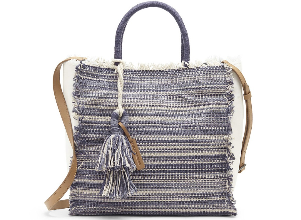 blue and white striped tote bag with brown crossbody strap and tassel on front
