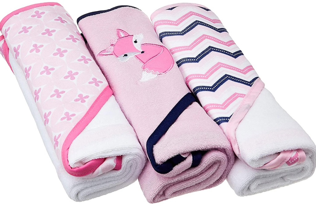 three rolled up baby towels in pink and white patterns with a pink fox