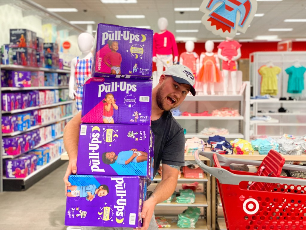 Man Holding Stack of Huggies Pull-Ups