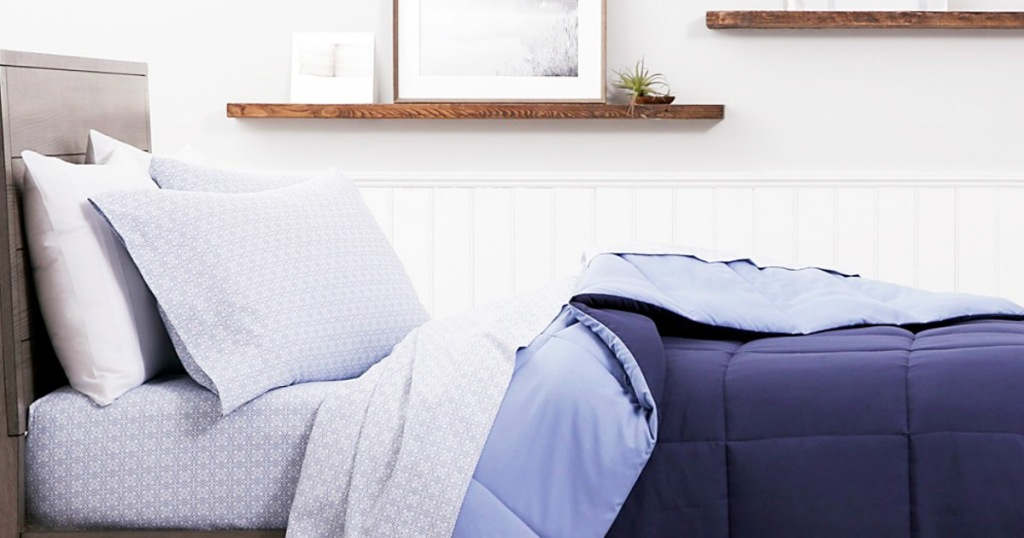 bed with printed sheet set and blue reversible comforter on it