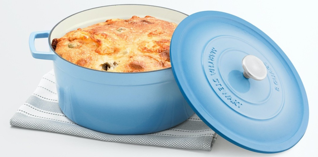 light blue dutch oven with food inside sitting on hand towel