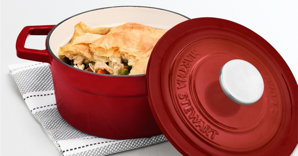 red dutch oven with food inside sitting on hand towel