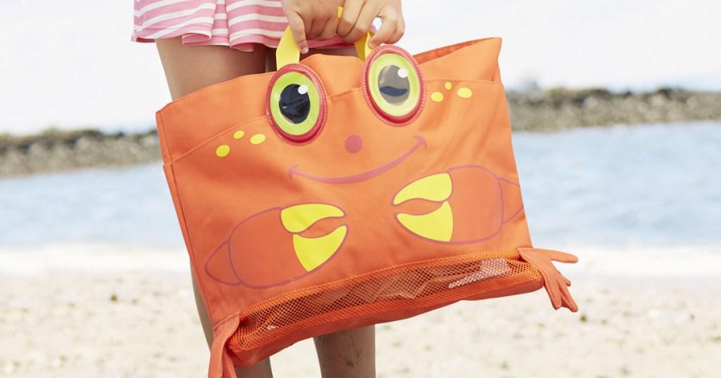 girl standing on beach holding an orange and yellow crab beach bag