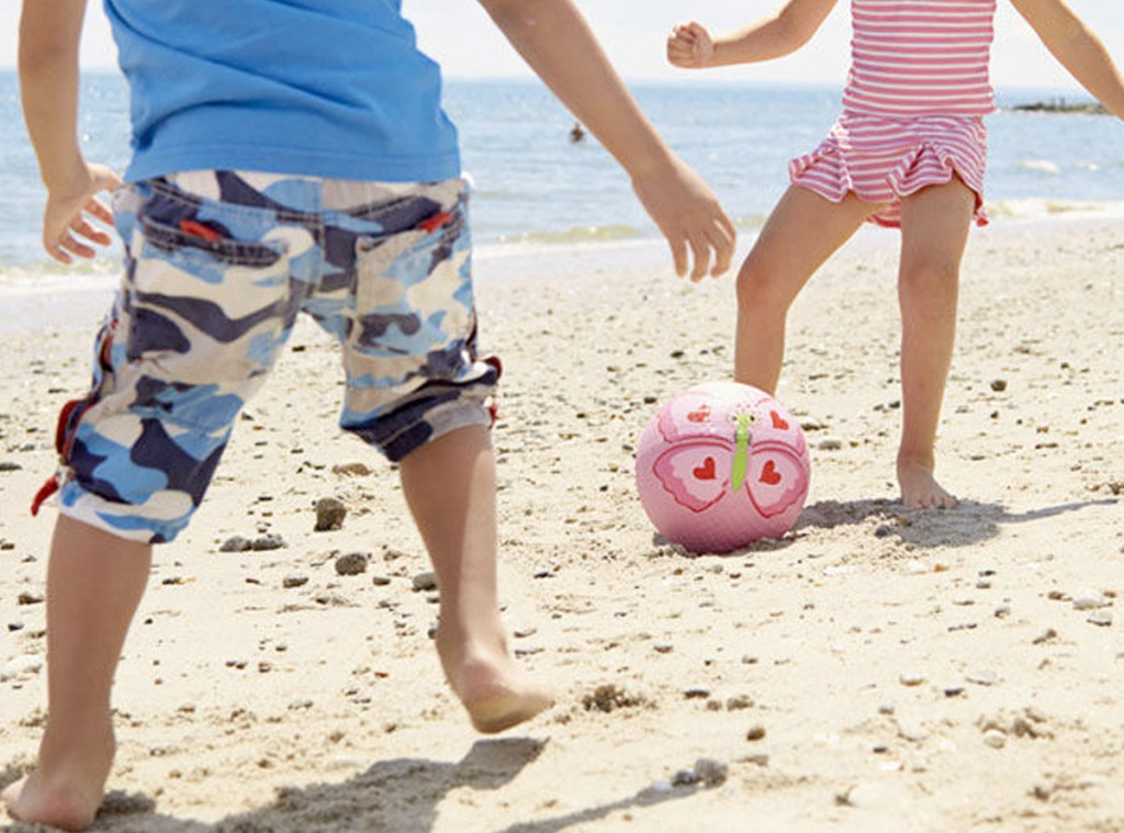 two kids kicking pink butterfly ball on beach