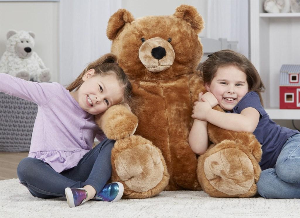 two girls sitting on playroom floor hugging a giant brown teddy bear