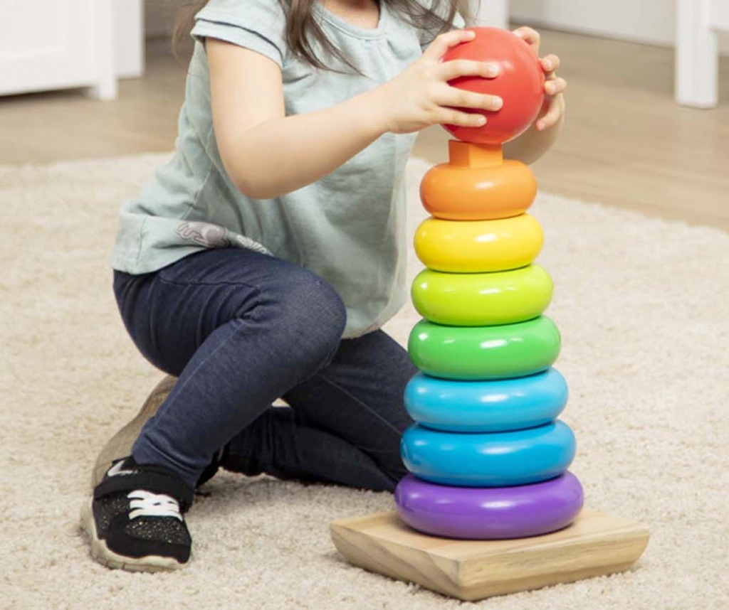 girl sitting on floor playing with a rainbow colored wooden stacker toy